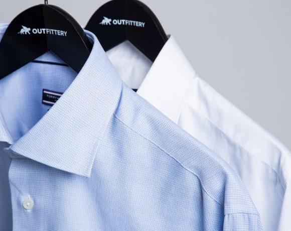 ein blaues und ein weißes Hemd hängen jeweils an einem Kleiderbügel mit dem Logo von Outfittery